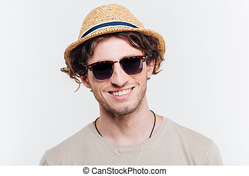 closeup, de, alegre, homem jovem, em, chapéu, e, óculos de sol, sorrindo