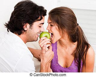 closeup, de, par jovem, morder, maçã verde