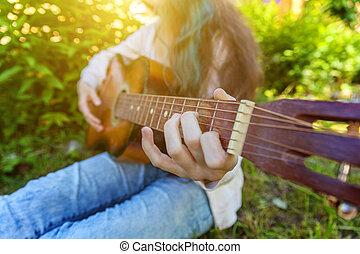 closeup, di, donna, mani, gioco, chitarra acustica, su, parco, o, giardino, fondo., ragazza adolescente, cultura, giocare, suonare, recitare, canzone, e, scrittura, musica