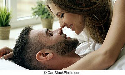 closeup, di, giovane, bello, e, coppia amorosa, gioco, e, bacio, letto, a, il, morning., attraente, uomo, baciare, e, abbracciare, suo, moglie, letto