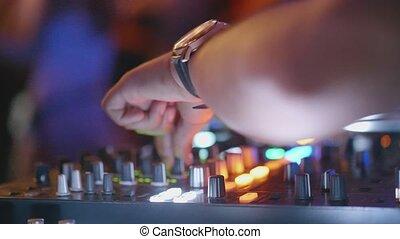 Closeup DJ hands mixes music at the party - Hands of man DJ...