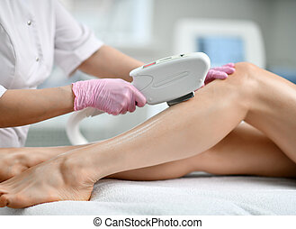 Closeup. Doctor-cosmetician in gloves performes a procedure on patient leg with medical equipment laser in equiped beauty shop