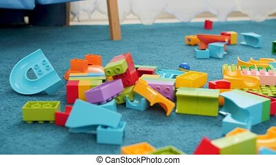 Closeup dolly footage of messy floor at childs room at house...