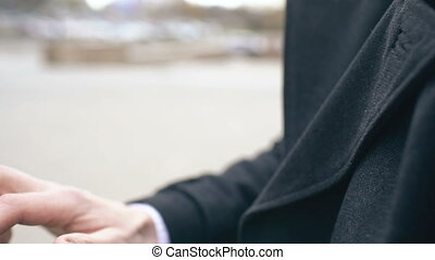 Closeup dolly shot of businessman face and hand using his smartwatch touchscreen standing on the street