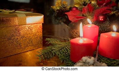 Closeup dolly shot of three burning candles and Christmas...