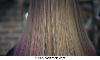 Closeup down-up view on dyed pink and blonde woman's hair in...