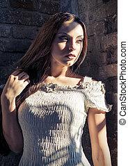 Closeup dramatic portrait of beautiful young woman in white dress