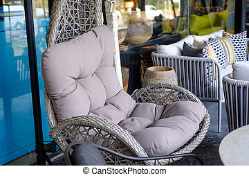 Closeup Empty hanging wicker Comfortable chair with pillow.