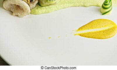 closeup exquisite decorated fried fish dish with sliced zucchini and green puree garnish spinning around on wooden table