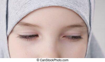 Closeup eyes of muslim teen girl in hijab looking at camera....