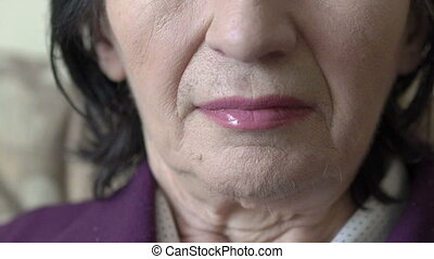 Closeup face of old woman looking on a camera. Slow motion
