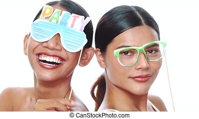 Portrait of two young smiling Asian women posing with props glasses over white background. Party, photo booth, friendship, fun time concept