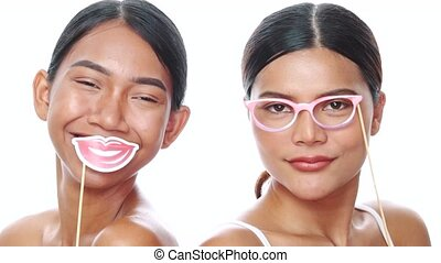 Portrait of two young smiling Asian women posing with props glasses and lips over white background. Party, photo booth, friendship, fun time concept