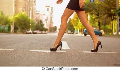 Closeup fashionable woman crosses the road