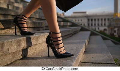 Closeup feet in high heels stepping down stairs - Close-up...