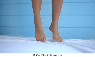 Closeup feet of young woman jumping on bed in slow motion -...