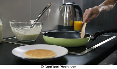 Closeup female hand flipping pancake on frying pan -...