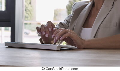 Closeup female hands using pc in office.