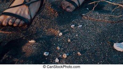 Closeup female legs walking on the black sand beach with sea shells