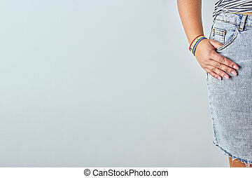 Closeup female palm in pocket with rainbow bracelet with text PRIDE