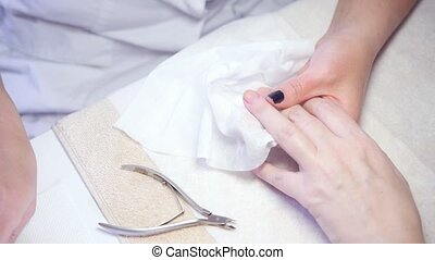 Closeup finger nail care by manicure specialist in beauty...