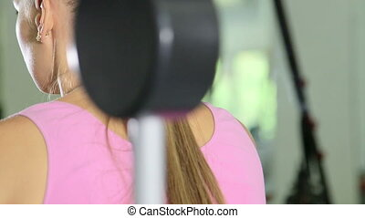 Closeup fit woman working out in health fitness club on leg curl machine