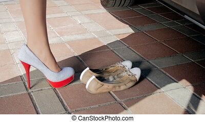 Closeup footage of female feet walking to the car and...