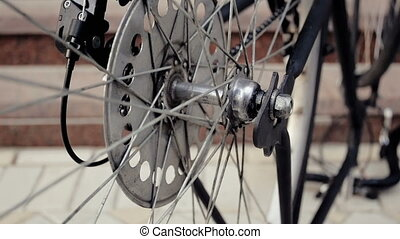 Closeup footage of old bicycle wheel slowly rotating -...
