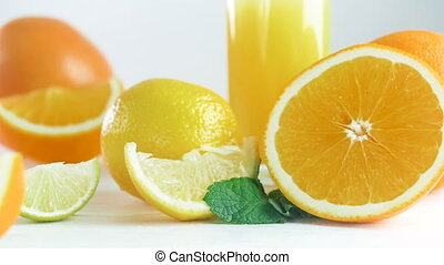 Closeup footage of oranges, limes, lemons and glass of...