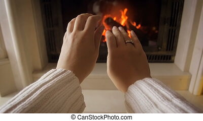 Closeup footage of young woman warming her hands at burning fire on cold winter day