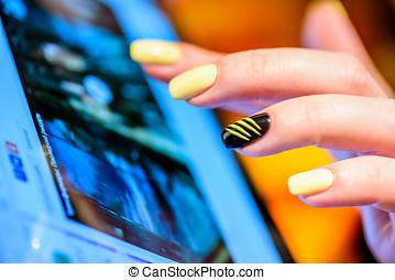 closeup, frau reicht, finger, mit, gelber , nägel, aus, tablette, schirm