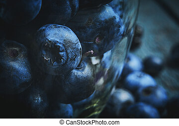 Summer food background. Close up fresh blueberries in glass jar on a dark wooden background. Macro with selective focus