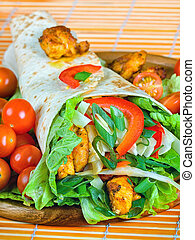 Healthy summer meal, grilled chicken and vegetables wrapped in a whole wheat tortilla