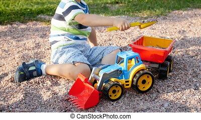 closeup, garçon, peu, pelle, plastique, chargement, vidéo, 4k, jouet, gravier, enfantqui commence à marcher, caravane