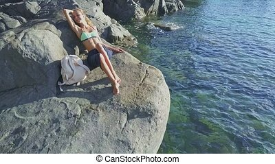 Closeup Girl Bakes in Sun on Rock against Transparent Ocean