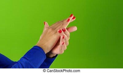 Closeup. Girl doing applause her hands on green screen...