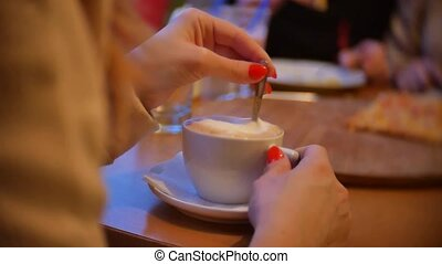 Closeup girl of hands with coffee cups in a cafe indoors -...