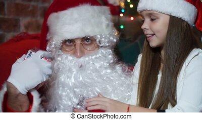 Closeup girl receives a gift from Santa Claus