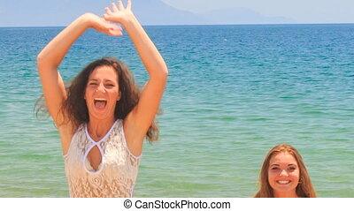 closeup girls cheerleaders jump gambol against azure sea