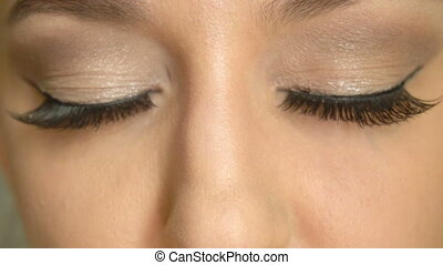 Closeup girls's face with closed eyes and long false lashes....