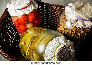 closeup glass jars with homemade canned vegetables lie in basket