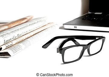 closeup glasses near financial newspaper in front of a unfocused notebook