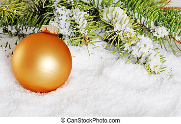 gold christmas ball in snow