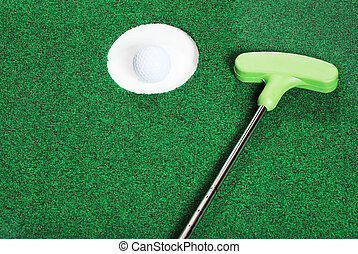 golf ball in the cup with putter