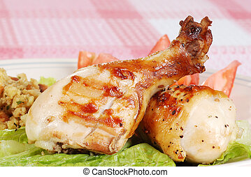 closeup grilled chicken drumsticks with pink and white tablecloth