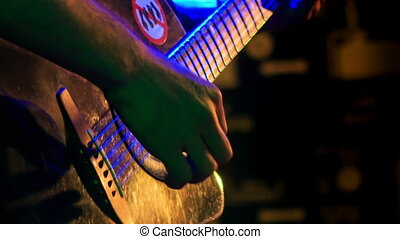 Closeup Guitarist Plays Guitar in Night Club at Light Flashes