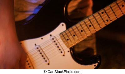 Closeup Guy Plays Guitar in Low Pose in Night Bar
