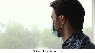 Close up serious guy put on disposable blue medical face mask looking out the window feels concerned. Corona virus pandemic outbreak, caution preventive measures stop covid-2019 and quarantine concept