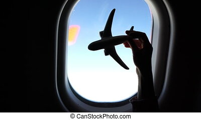 Closeup hand holding an airplane model toy background window at aircraft