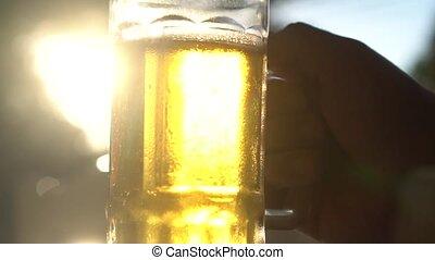 Closeup hand holding lager beer mug with sun rays